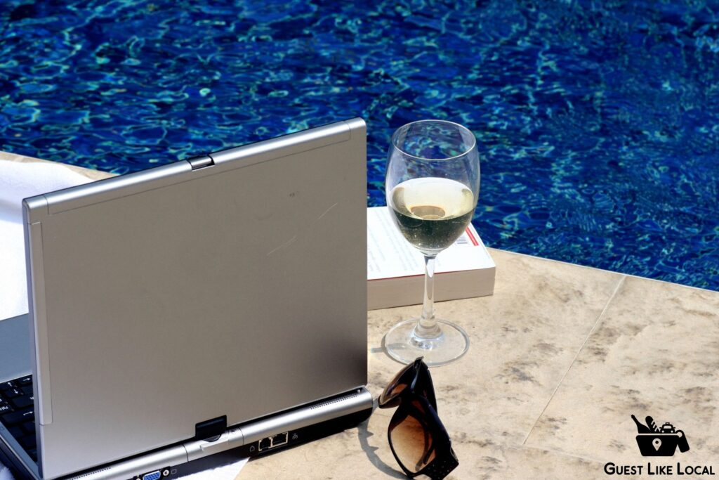 Laptop and glass of wine next to the pool